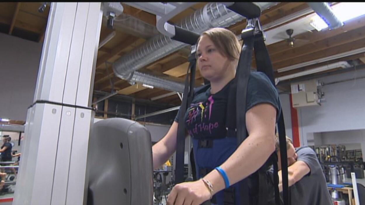 Une femme avec un handicap s'entraîne sur un tapis roulant.