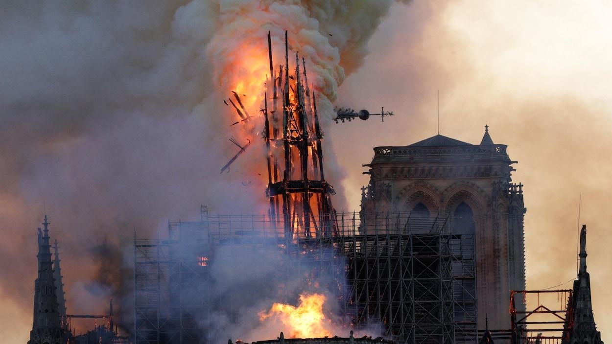 La flèche de la cathédrale, en feu, commence à s'écrouler.