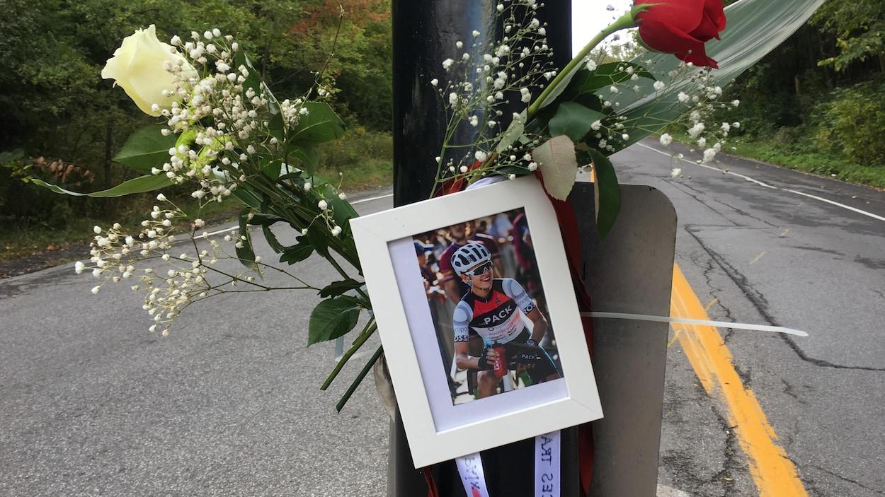 Des fleurs et une photo d'un cycliste mort après une collision, accrochées sur un poteau de la voie Camilien-Houde, sur le mont Royal, à Montréal.