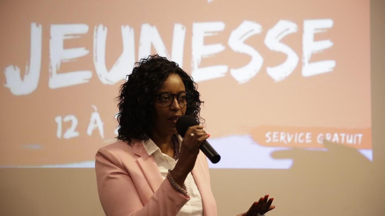 Une femme avec un veston rose et une chemise blanche parle dans un microphone devant un écran projecteur.