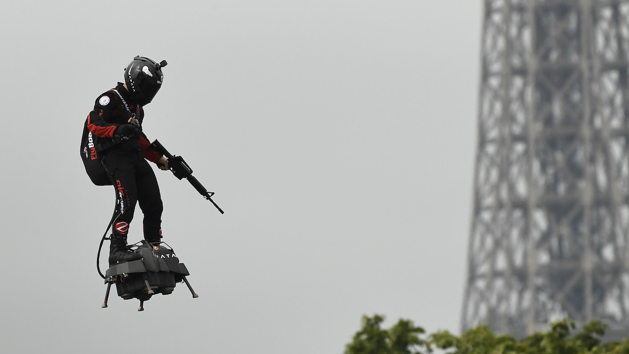 Un homme en combinaison et portant un casque vole à l'aide d'une petite plateforme noire accrochée à ses pieds. L'homme tient un fusil d'assaut dans sa main gauche. En arrière plan, une partie de la tour Eiffel est visible.