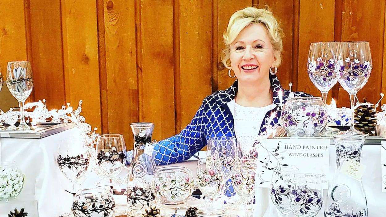 Une femme pose derrière une table remplie de coupes de vin peintes à la main.