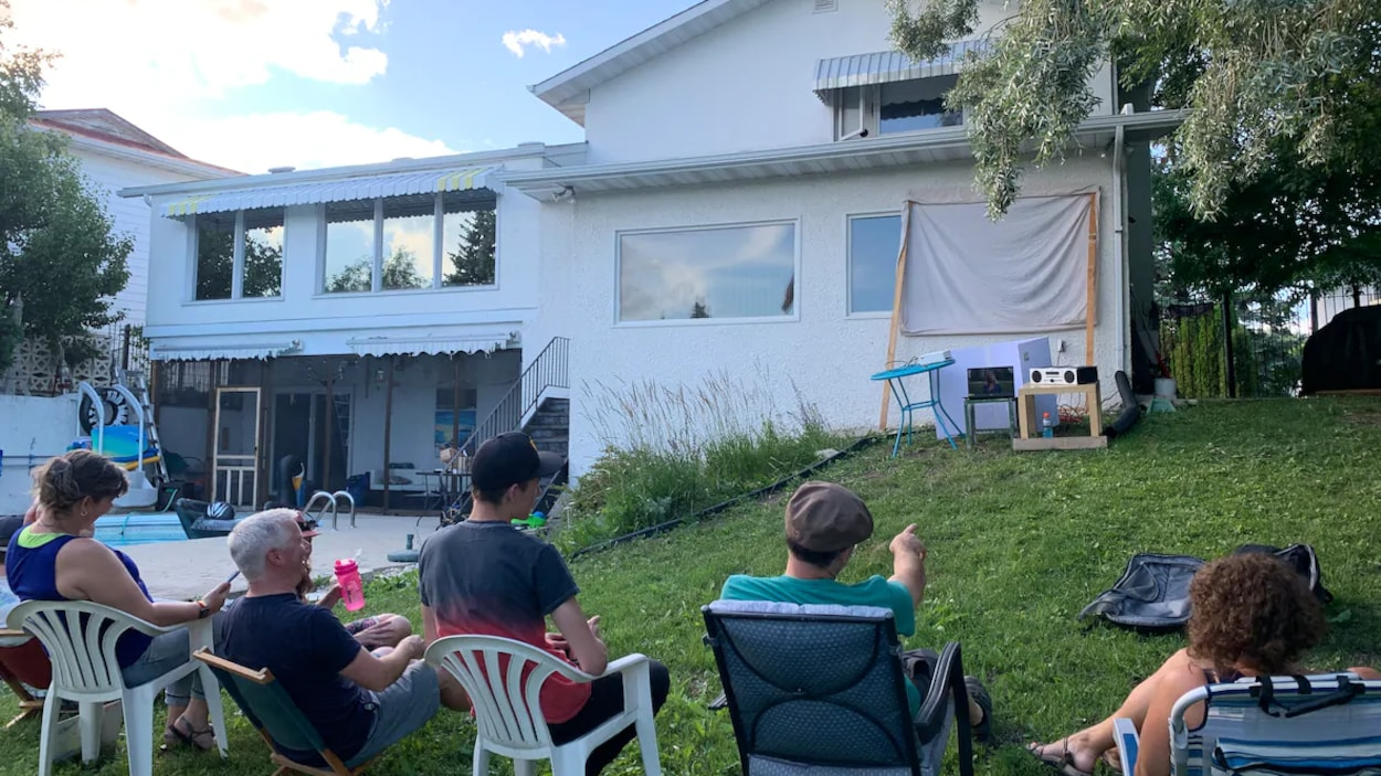 Cinq personnes sont assis sur des chaises et regardent un écran installé à l'extérieur dans la cour arrière d'une maison.