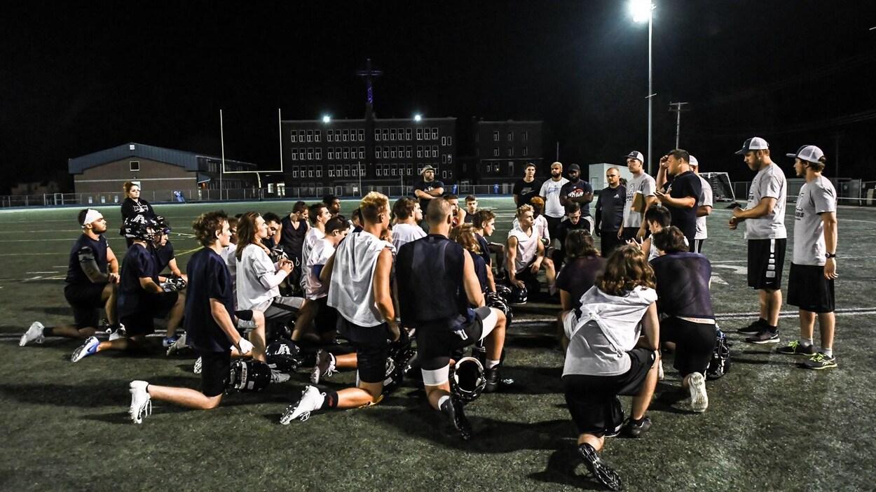 Les joueurs de football écoutent les directives de leur entraîneur.