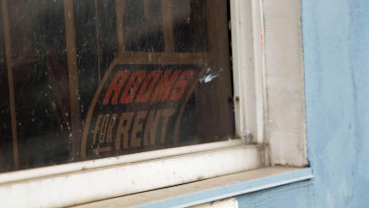 """Panneau """"for rent"""" affiché à la fanêtre d'une habitation."""
