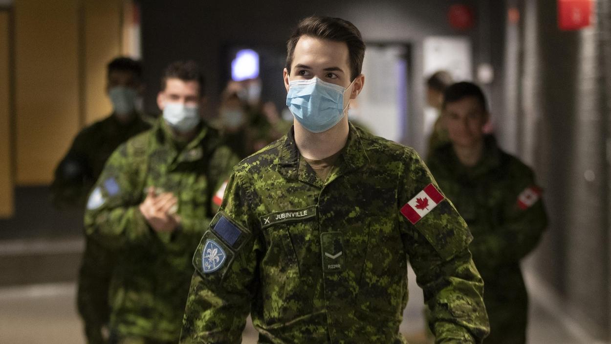 Des militaires des forces armées canadiennes, la plupart portant un masque, dans un couloir d'un collège.