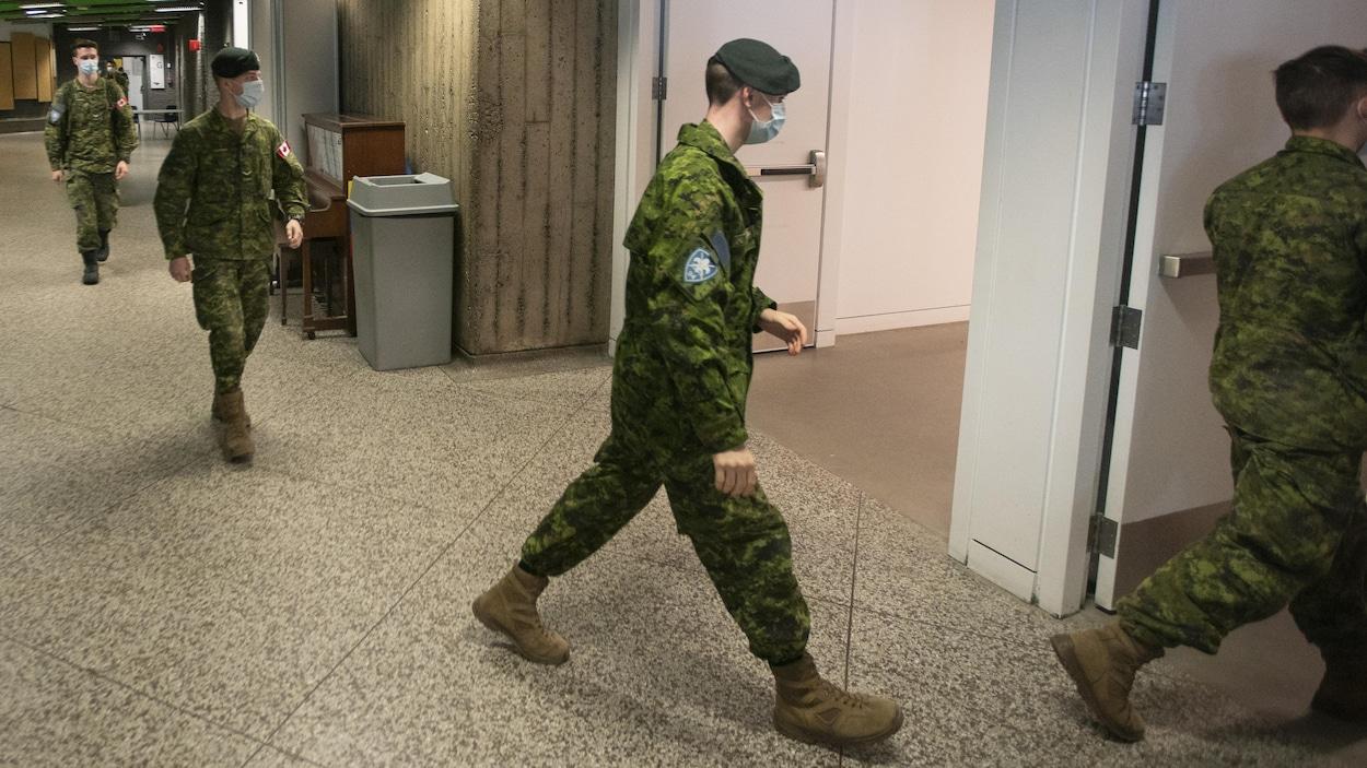 Des militaires portant un masque respectent une bonne distance entre eux.