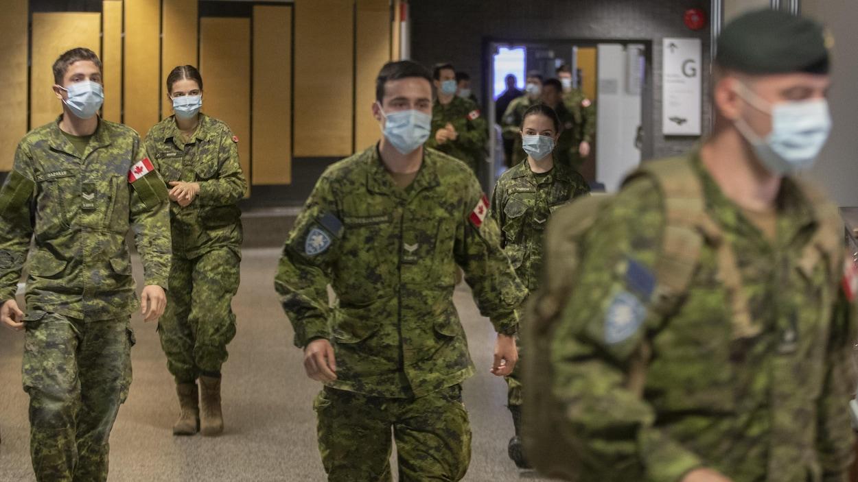 Des militaires portant un masque marchent dans un édifice.