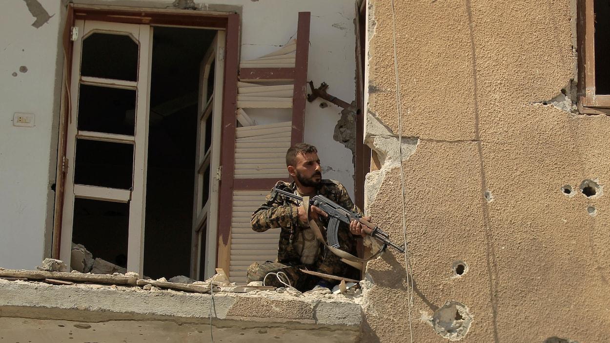 Un combattant est accroupi sur le balcon d'un immeuble en ruines.