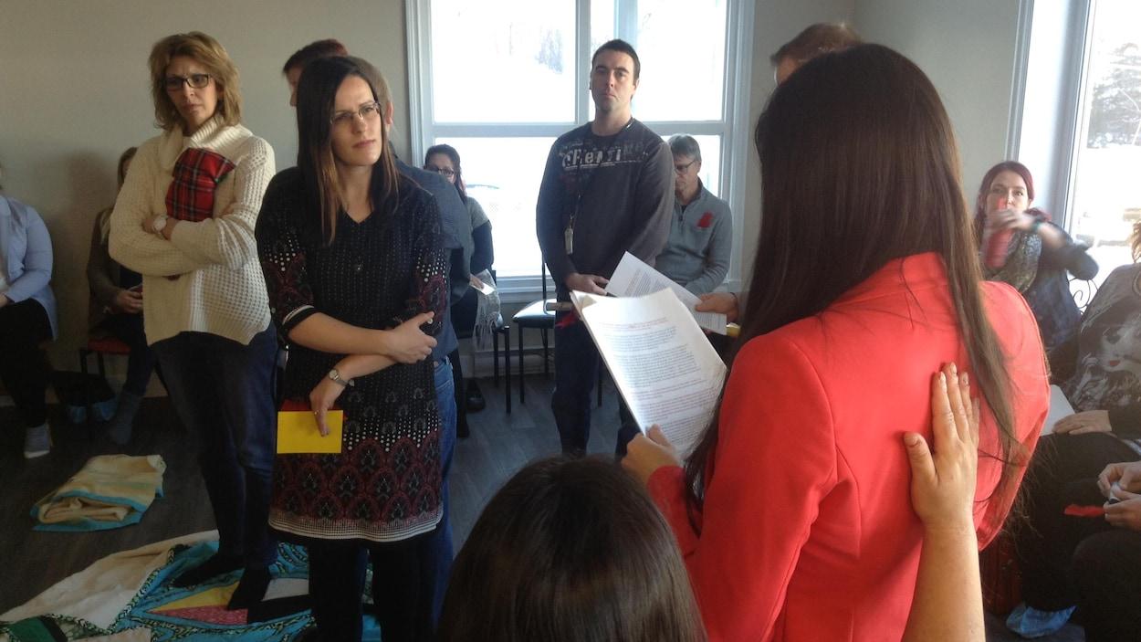 La narratrice Jessica Nanipou fait la lecture de l'histoire autochtone à des intervenants en santé qui l'écoutent attentivement debout dans la salle de formation.