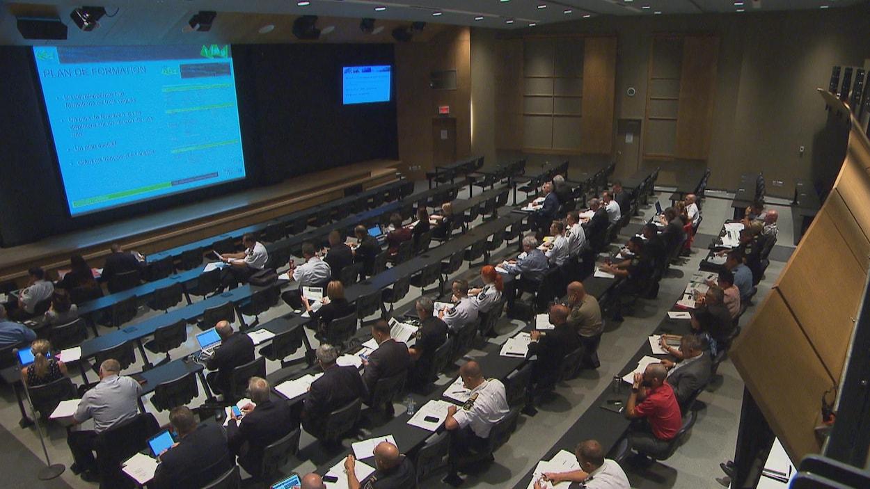 Près de 100 personnes assises dans une salle de l'École nationale de police du Québec pour suivre une formation.