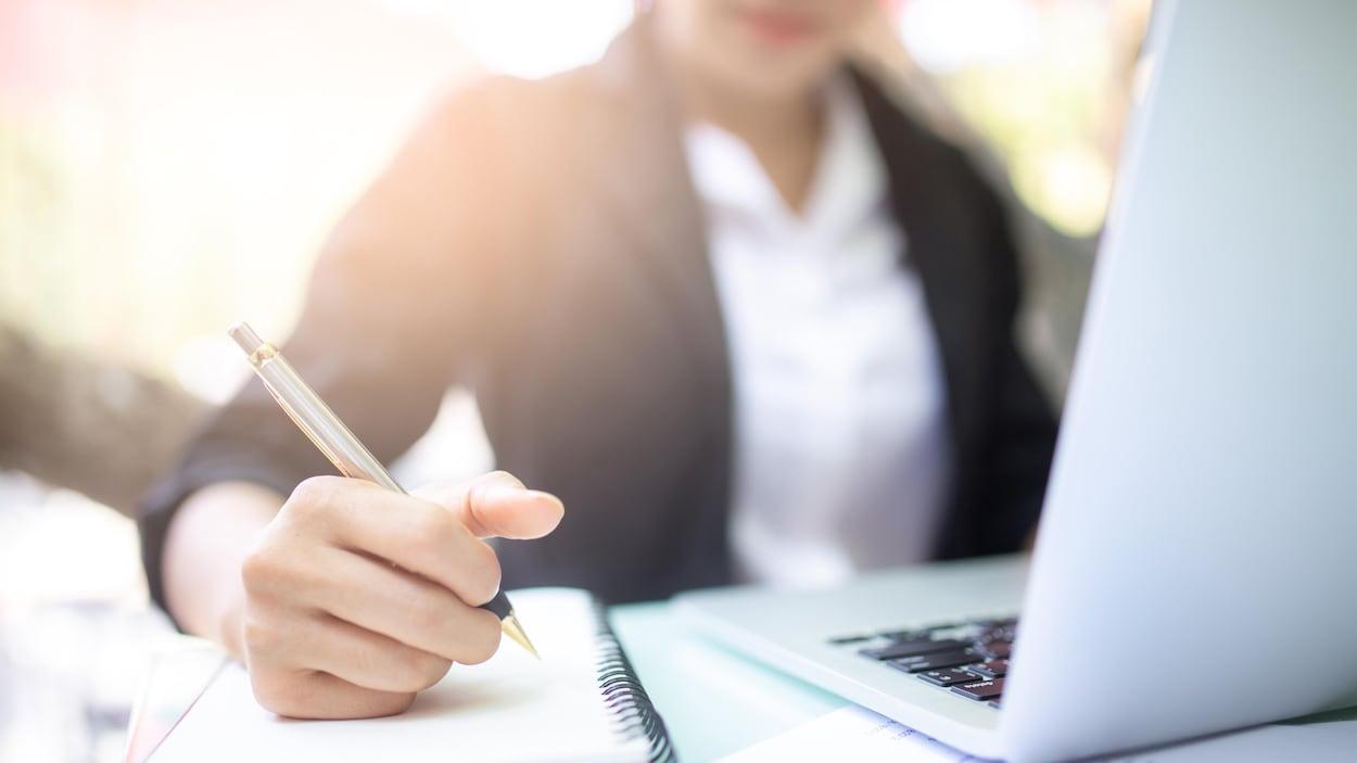 Une travailleuse assise devant un ordinateur portable, un stylo à la main.