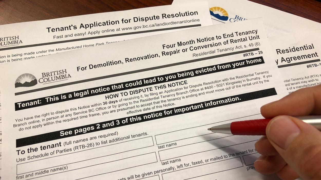 Un locataire remplit au stylo des formulaires gouvernementaux.
