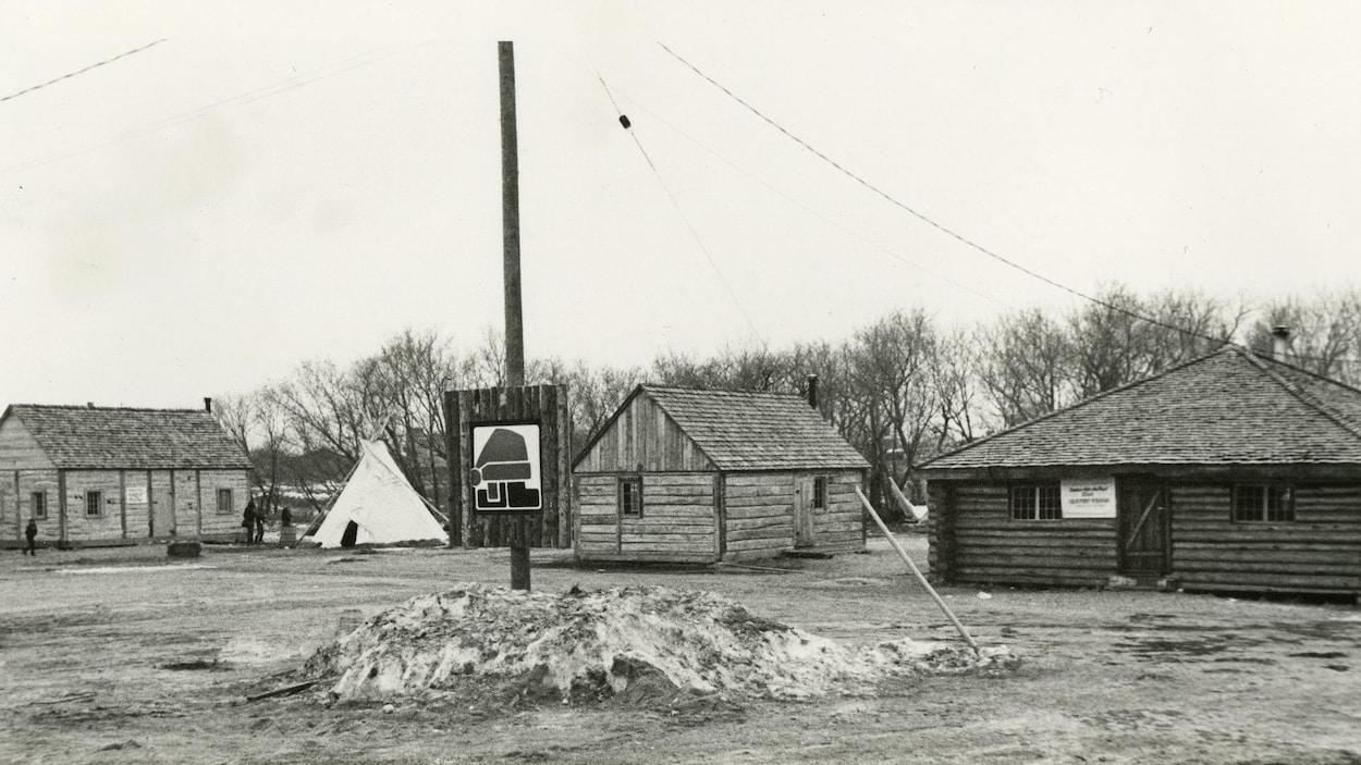 4 cabanes de bois rond dans la neige. Entre la deuxième et la troisième se dresse un tipi.