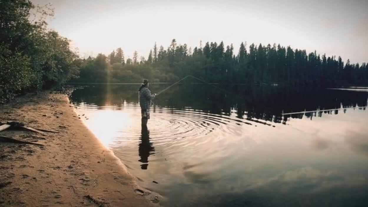 Vue sur un homme les pieds dans l'eau d'un lac et qui pêche