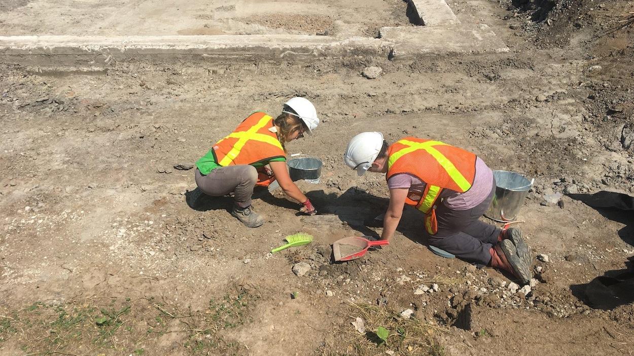 Deux personnes mènent des fouillent archéologique sur le terrain du futur pôle d'échange de transport en commun Saint-Roch à Québec