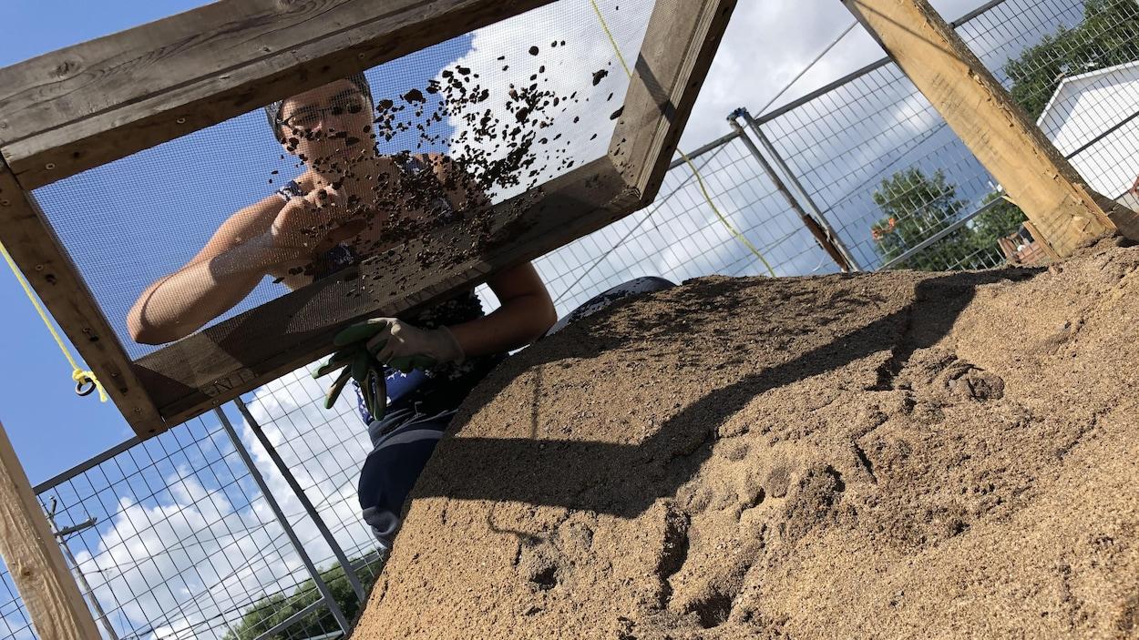 Hélèna Launière en train de tamiser des objets au-dessus d'un bac de sable.