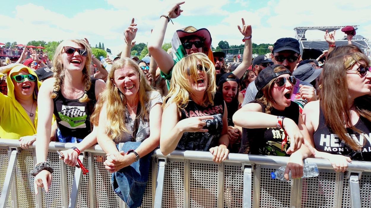 Des femmes souriantes et enthousiastes sont alignées le long d'une clôture lors d'un spectacle du Rockfest en plein soleil.