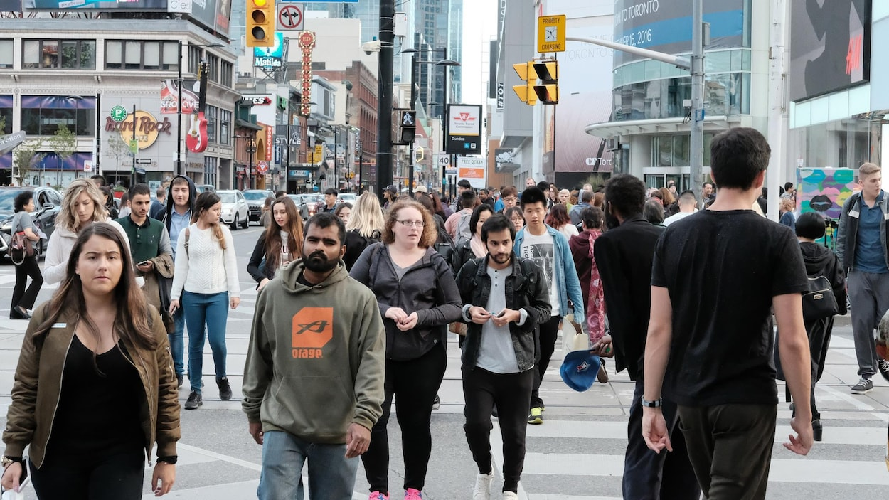 Des passants marchent dans la rue à Toronto.