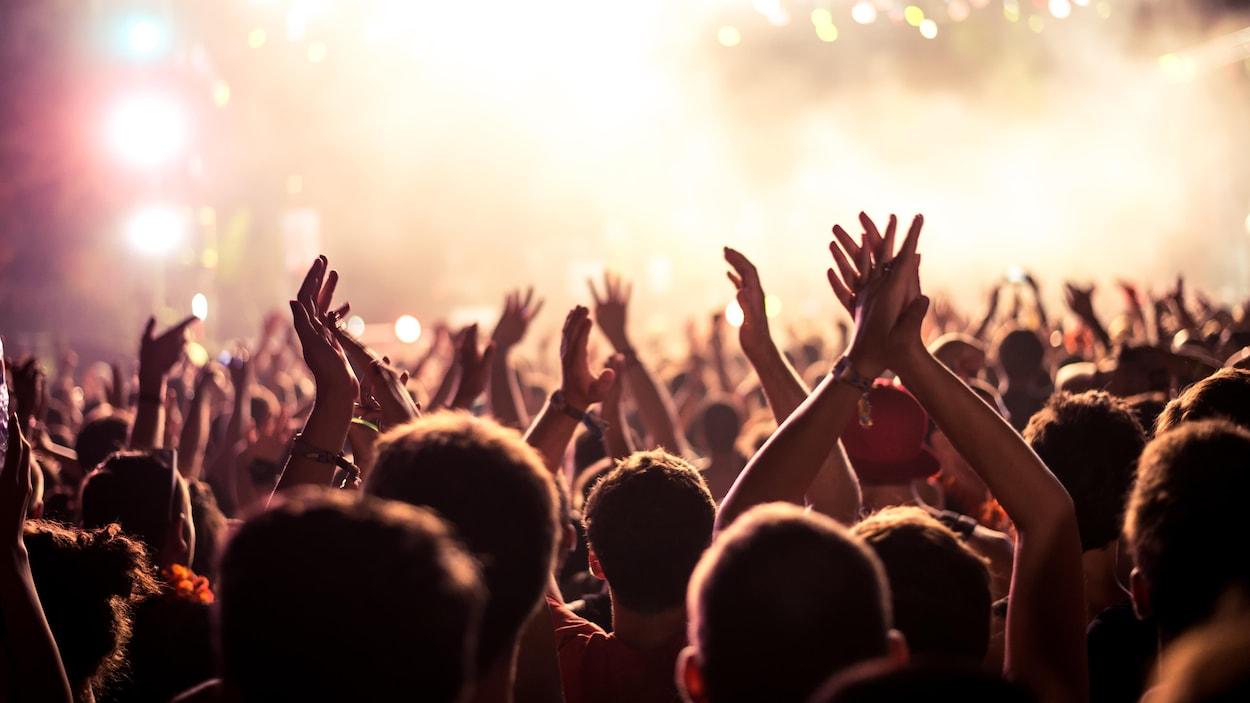 Des personnes les mains dans les airs au milieu d'une foule compacte, dans une salle où des lumières s'illuminent au-dessus de la scène.