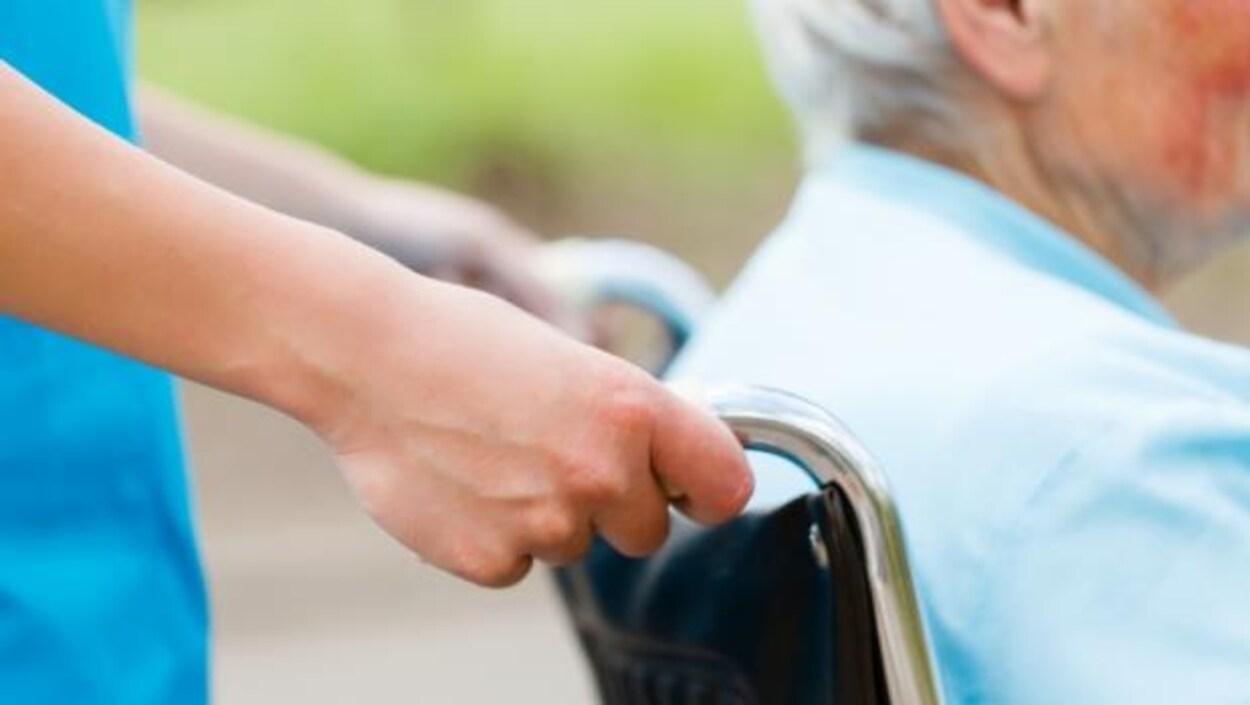 Une préposée aux soins aide un patient à se déplacer en fauteuil roulant