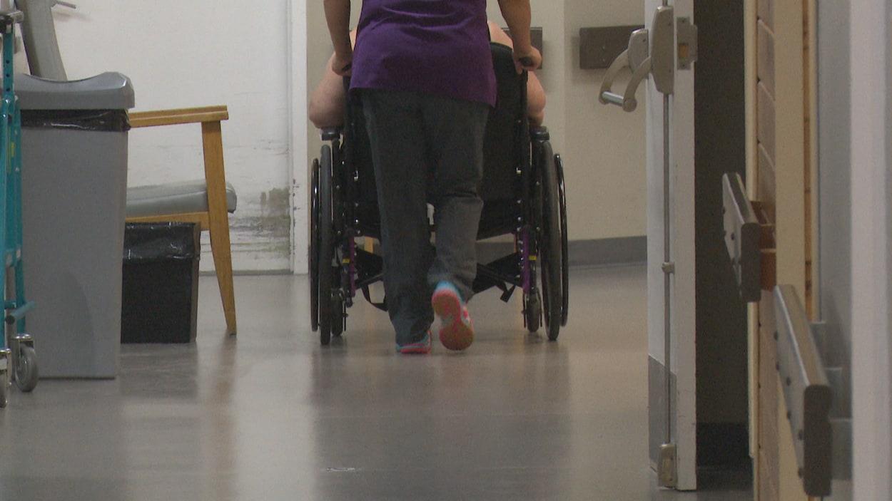 Une préposée aide un résident à se déplacer en fauteuil roulant dans un couloir du foyer de soins.