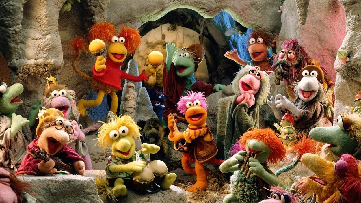 Les marionnettes de Fraggle Rock chantant et dansant dans une grotte.