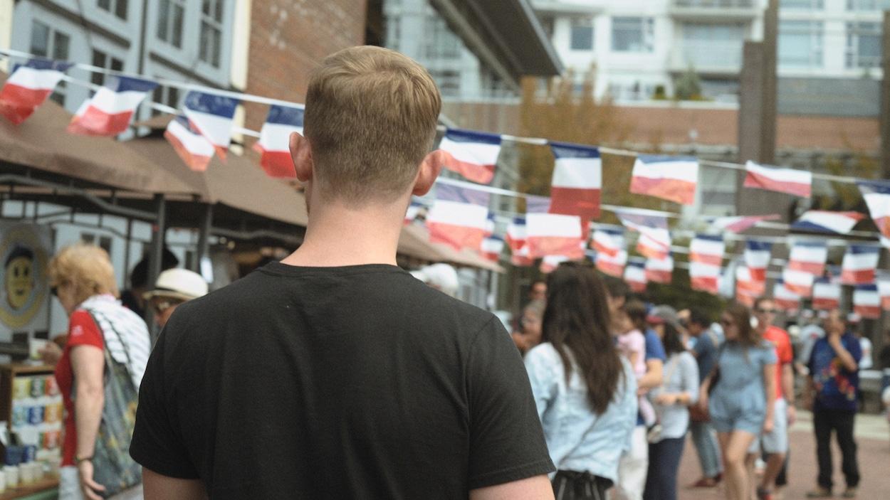 Un homme marche dans la foule. Des drapeaux français sont suspendus.