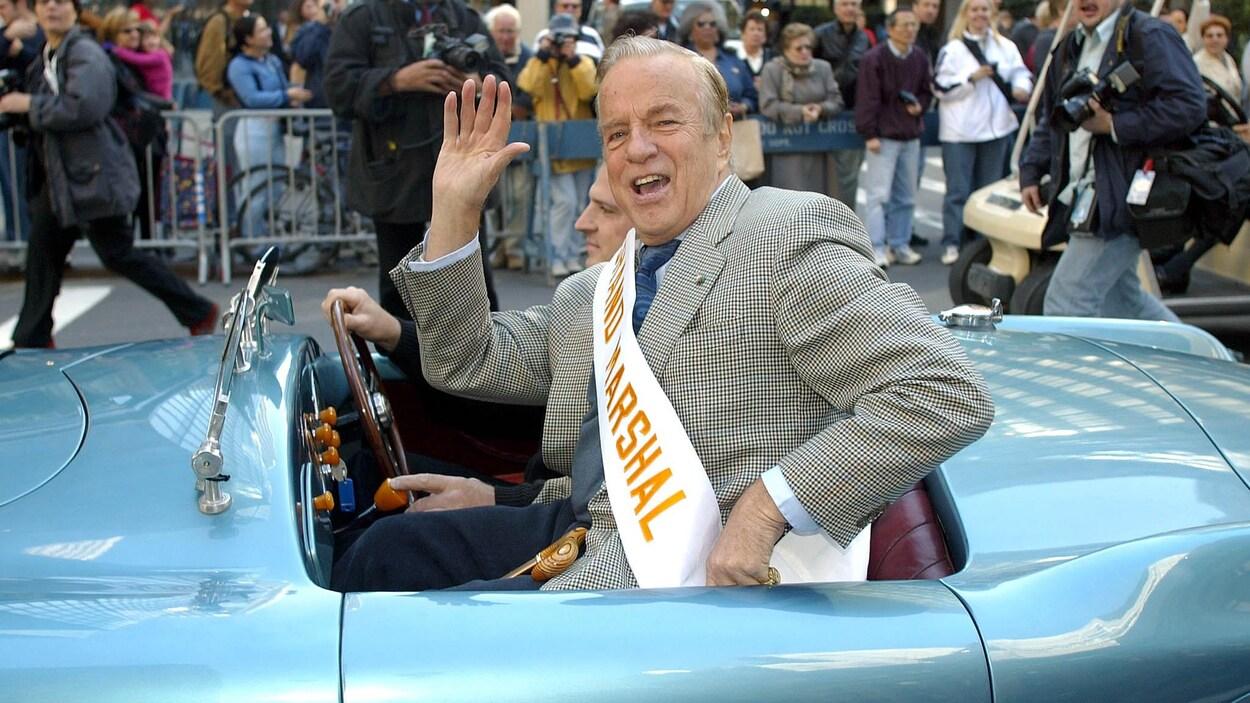Franco Zeffirelli, dans une voiture décapotable, salue la foule et les journalistes sur une rue de New York.