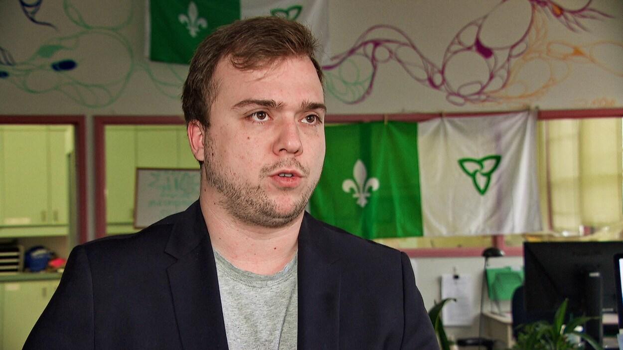 Un jeune homme en entrevue devant des drapeaux franco-ontariens.