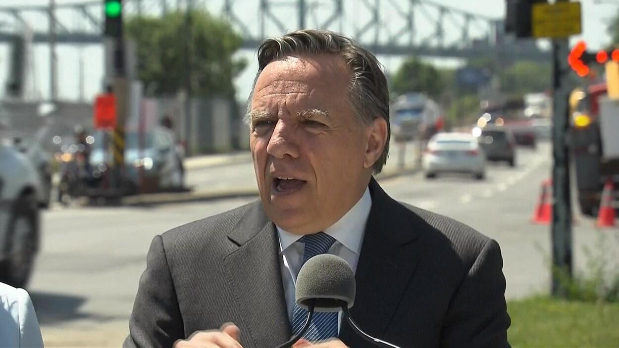 M. Legault s'adresse aux médias en bordure de la rue Notre-Dame, près du pont Jacques-Cartier.