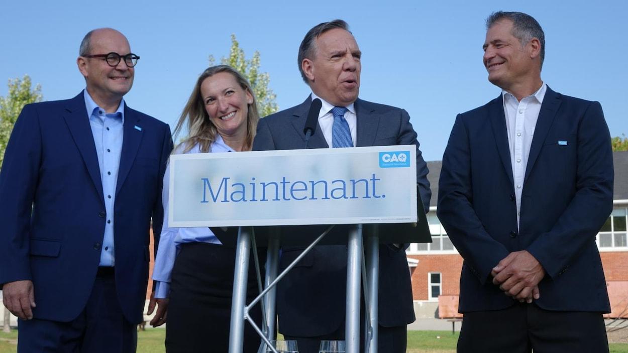 François Legault est entouré de trois candidats en point de presse devant une école de Vaudreuil.