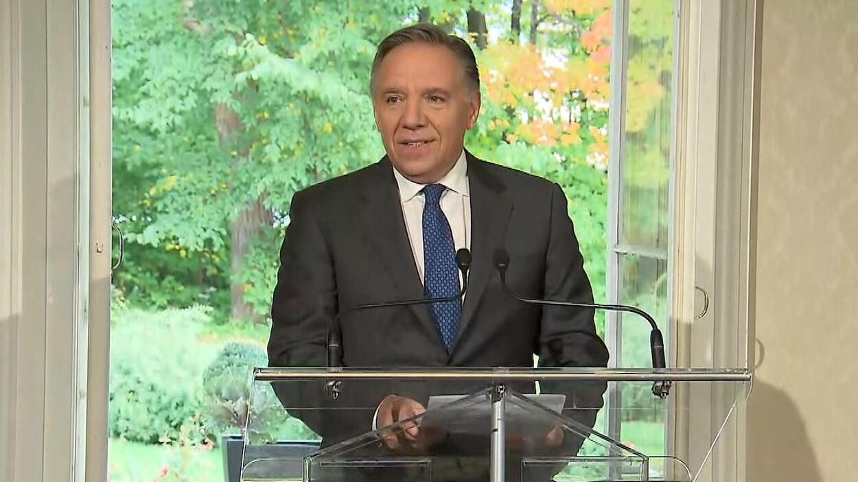 François Legault au podium, devant une fenêtre.