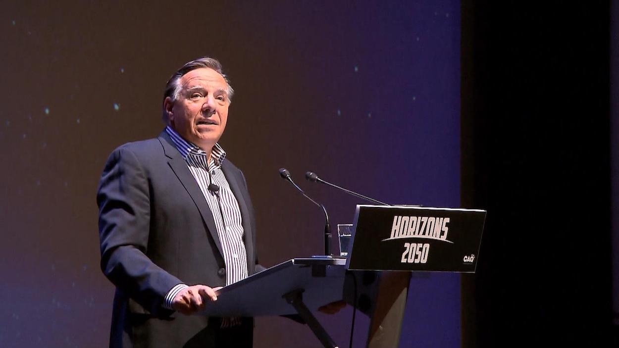 Un homme sur la scène d'un auditorium parle au micro derrière un lutrin où l'on peut lire : Horizons 2050.