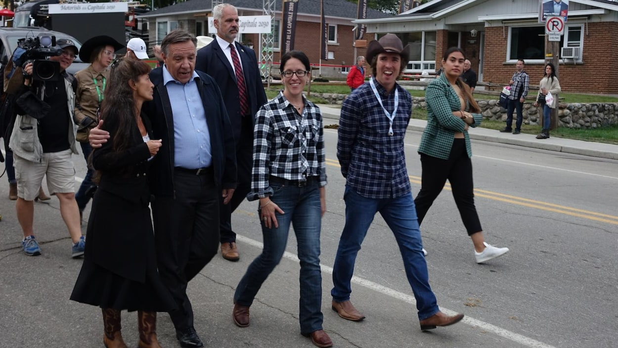 François Legault qui marche dans la rue aux côtés des candidats