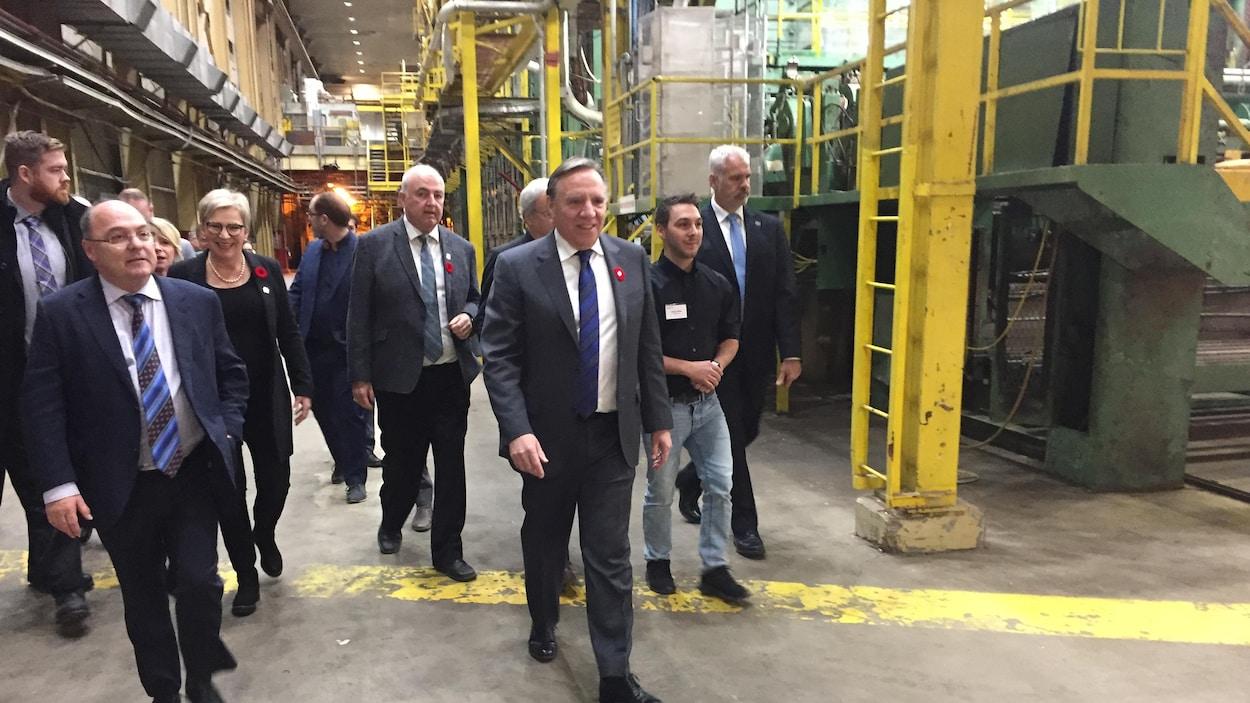François Legault marche à l'intérieur de l'usine de pâte accompagné de dix personnes.
