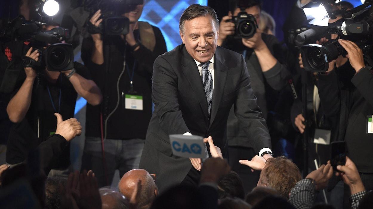 Le chef de la Coalition avenir Québec, François Legault, distribue les poignées de main à des militants de sa formation politique devant les caméras.
