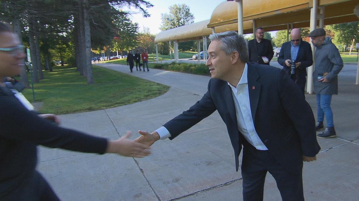 François-Philippe Champagne qui s'étire le bras pour serrer la main d'une électrice.
