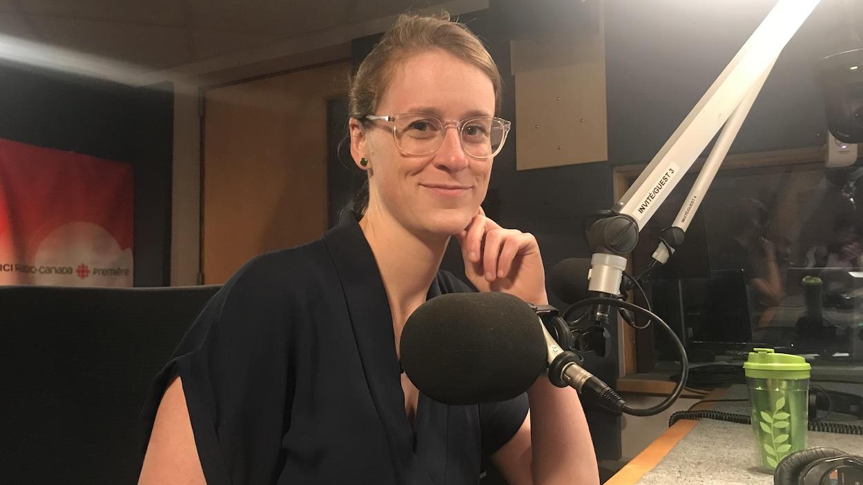 Une femme devant un micro dans un studio radio.