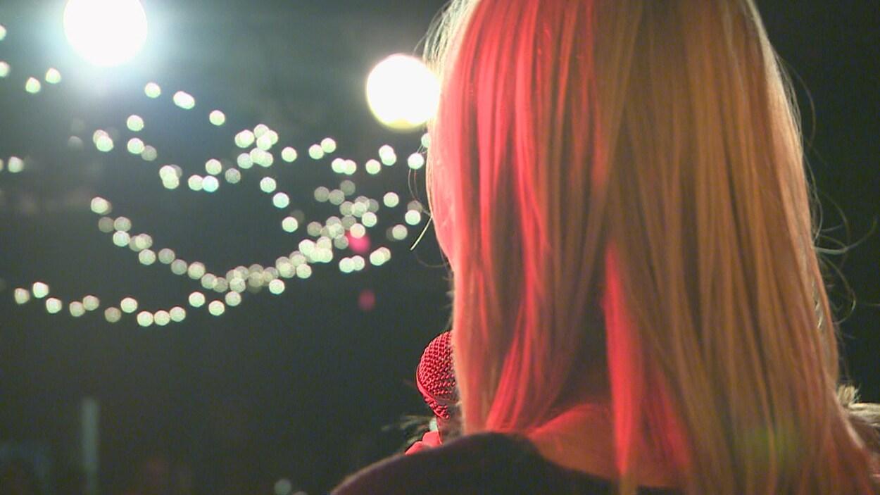 Une chanteuse qui tient un micro devant une foule dans la noirceur et des petites lumières.