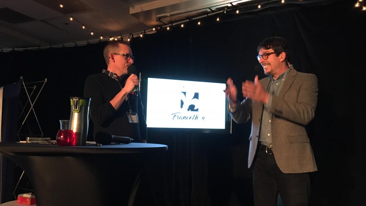 Deux hommes échangent, devant un écran télé et un rideau noir.