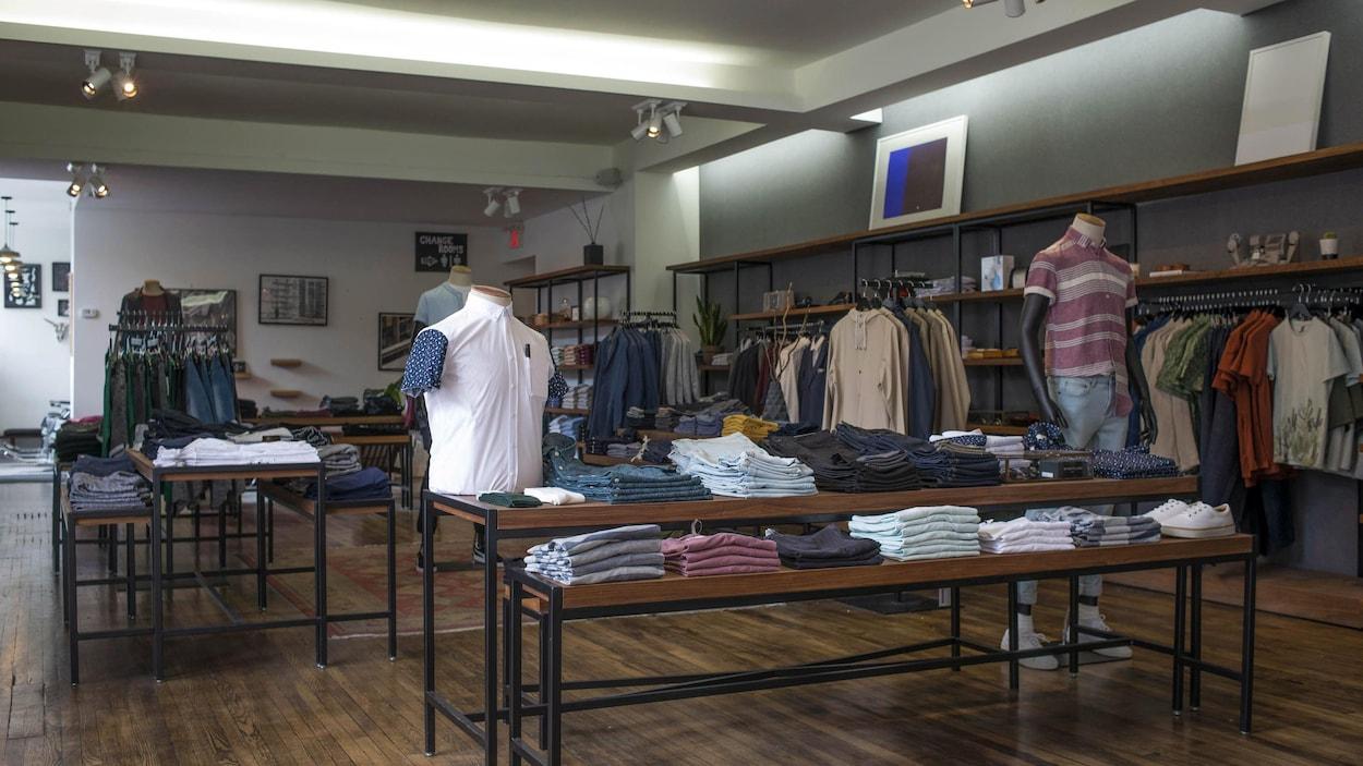 Des chemises et des chandails sont visibles dans un magasin.
