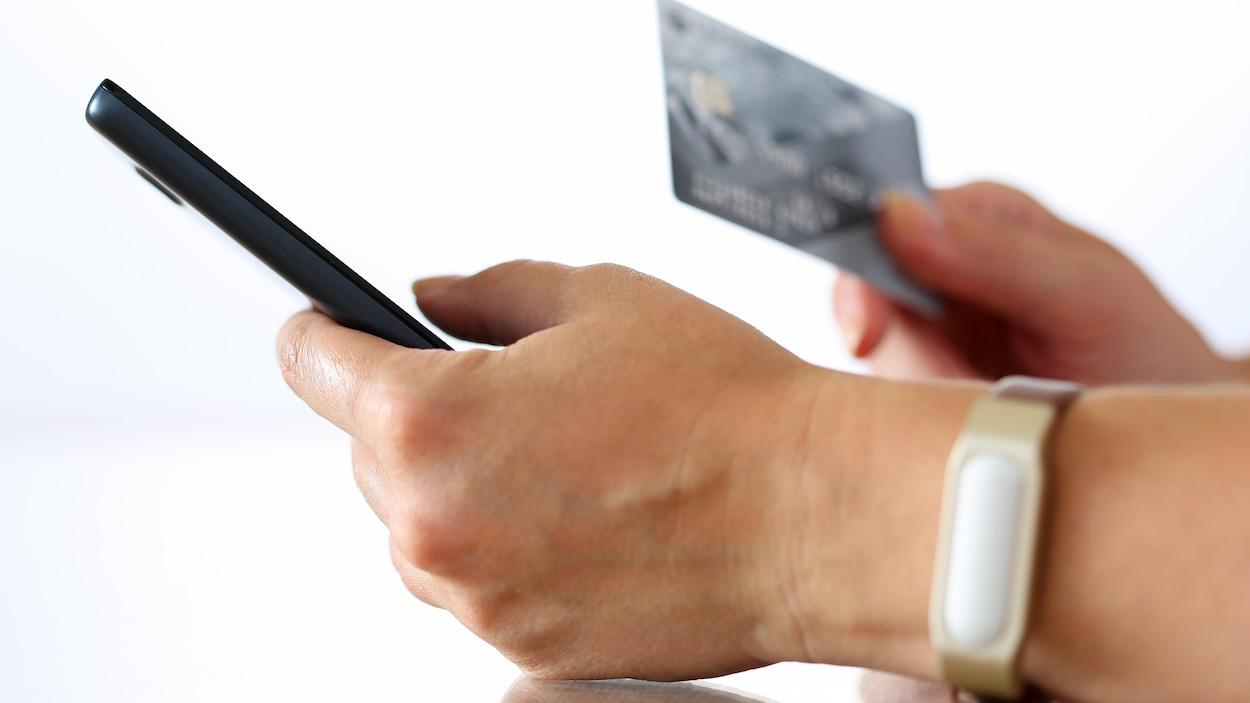 Mains qui tiennent un téléphone cellulaire et une carte de crédit.