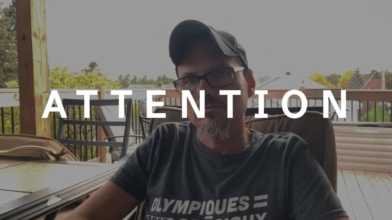 Un homme assis sur un balcon regarde la caméra. Le mot ATTENTION est superposé sur la photo.