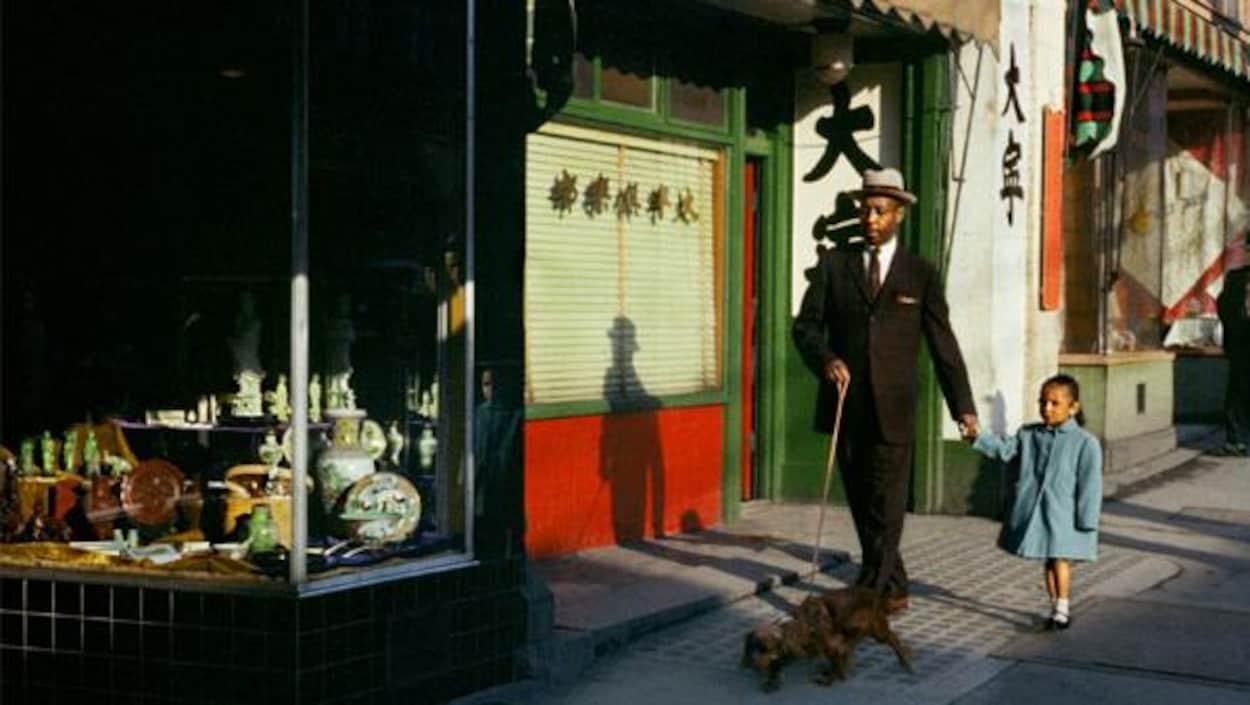 Un homme se promène dans une rue avec sa fille et son chien en laisse.