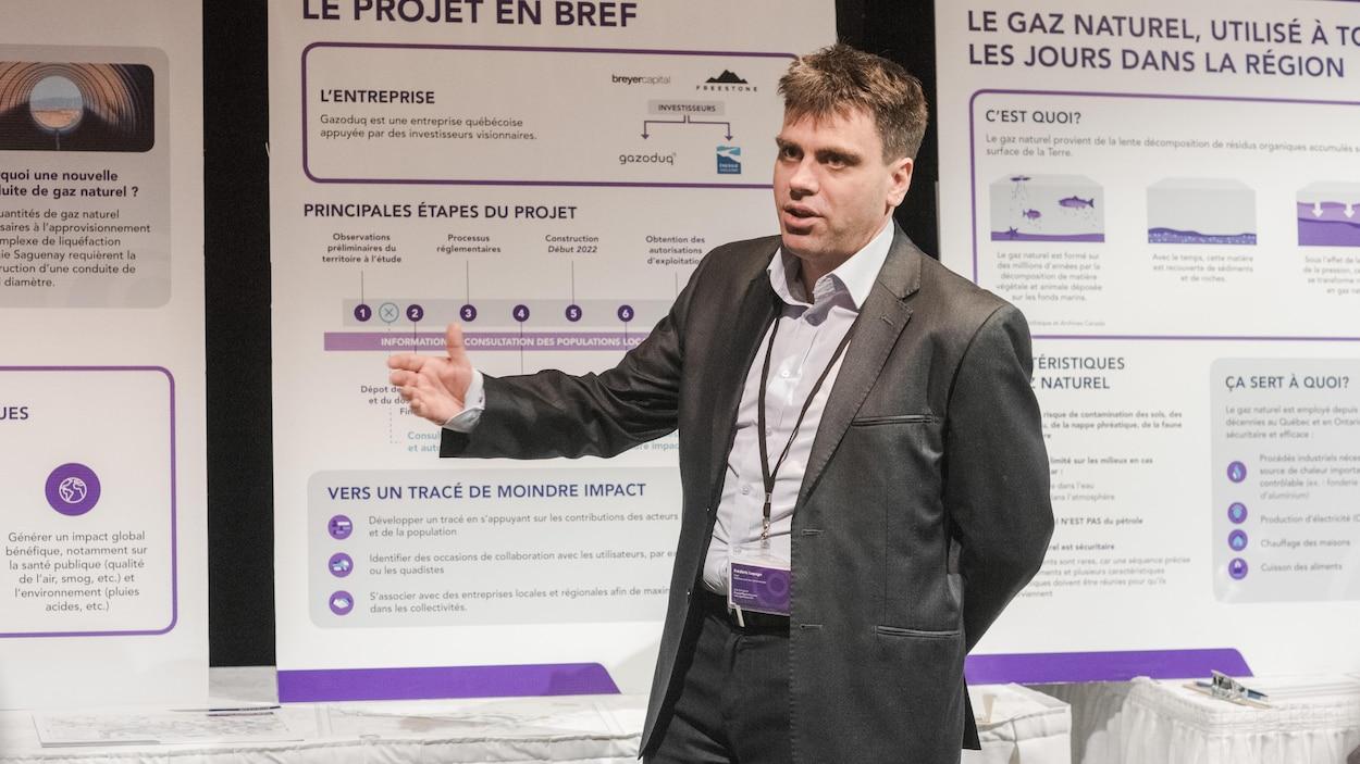 Un homme parle devant une foule lors d'une consultation de l'entreprise Gazoduq.