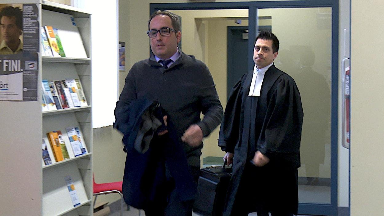 Homme qui marche avec un avocat derrière lui.