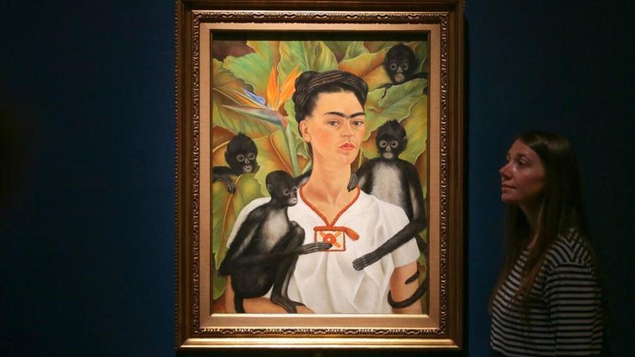 Le tableau, exposé sur un fond bleu, représente Frida Kahlo entourée de 4 petits singes noirs.