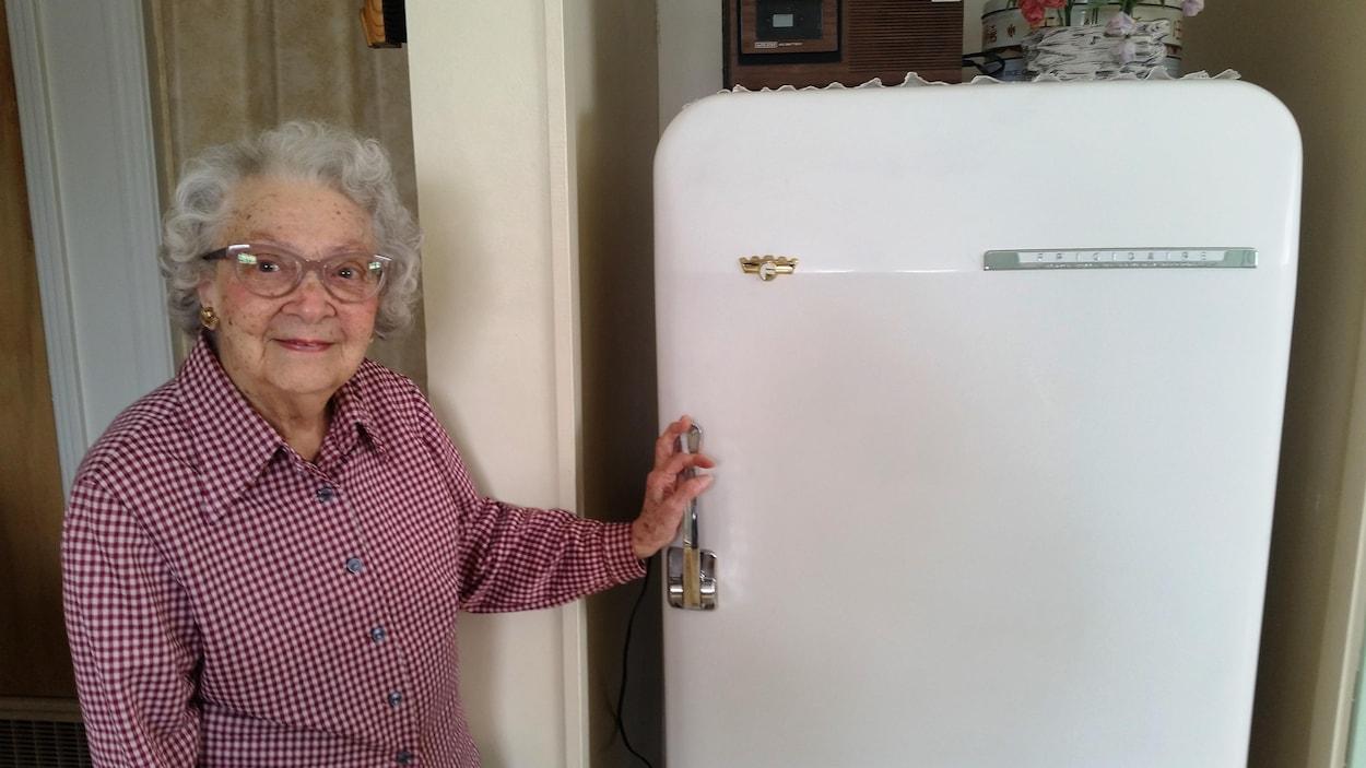 Une dame âgée, coquette, a la main sur la poignée de son vieux frigo qui date de 1953.