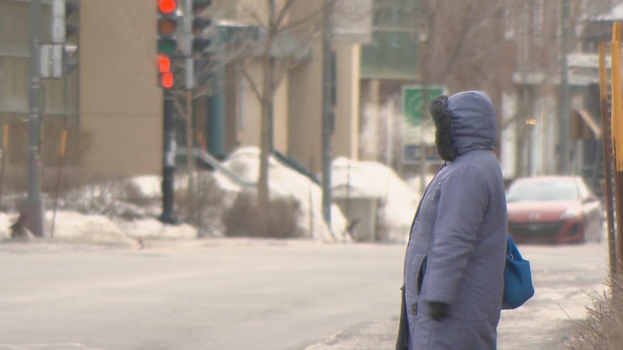 Une dame attend sur le trottoir vêtue d'un gros manteau d'hiver